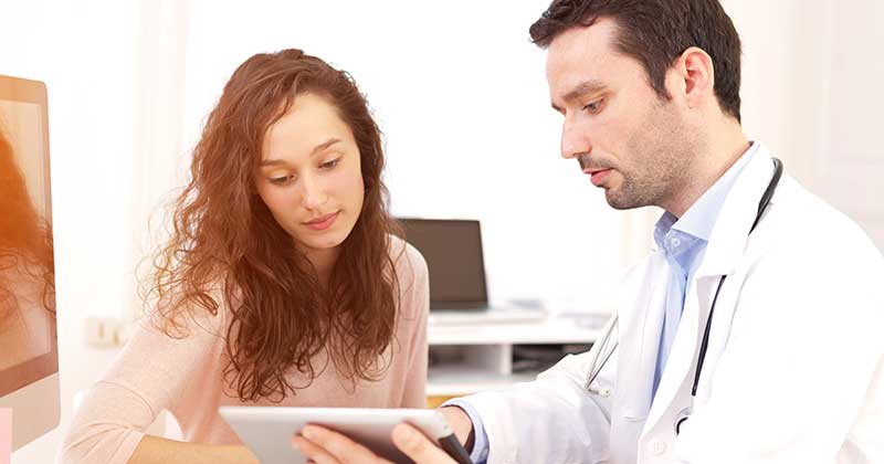 Doctor showing a patient information with an iPad