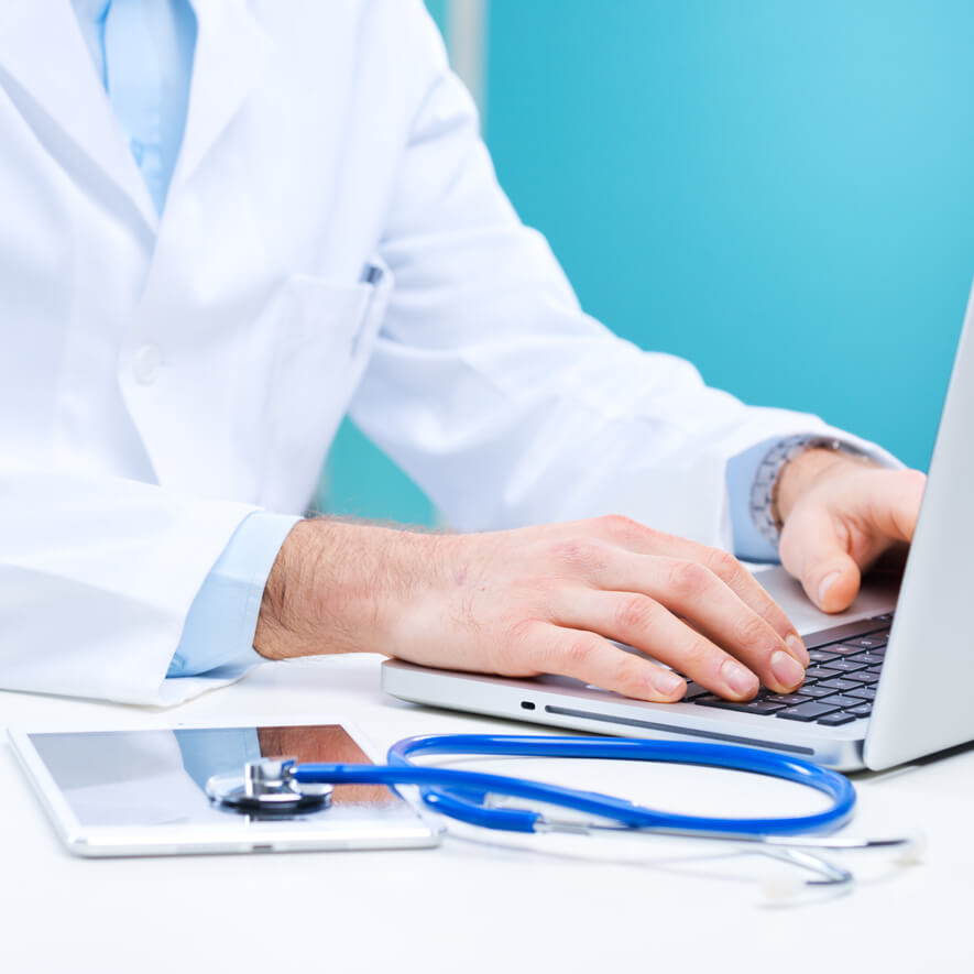 A doctor typing on his laptop at his desk