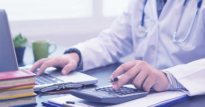 Doctor calculating with medical billing software